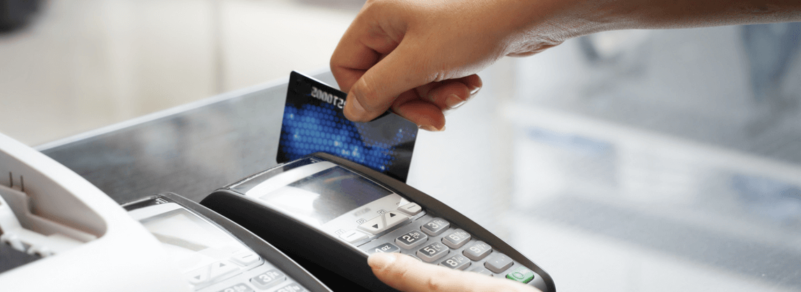 A hand swiping a debit or credit card